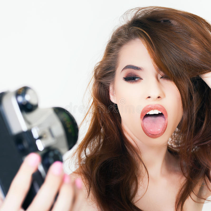 Funny girl make a foto selfie at vintage camera. Image of funny girl, show tongue, make a foto selfie at vintage camera. Take a photograph of herself. Fun royalty free stock images