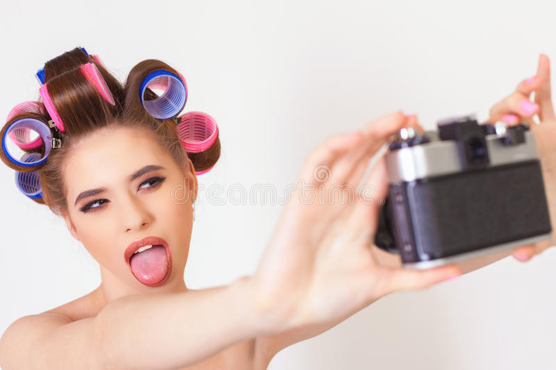 Funny girl make a foto selfie at vintage camera. Image of funny girl make a foto selfie at vintage camera. Take a photograph of himself. Fun, party. Beauty stock photos