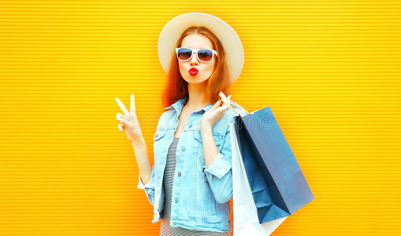 Funny girl makes an air kiss holds a shopping bags in straw hat. On orange background stock images