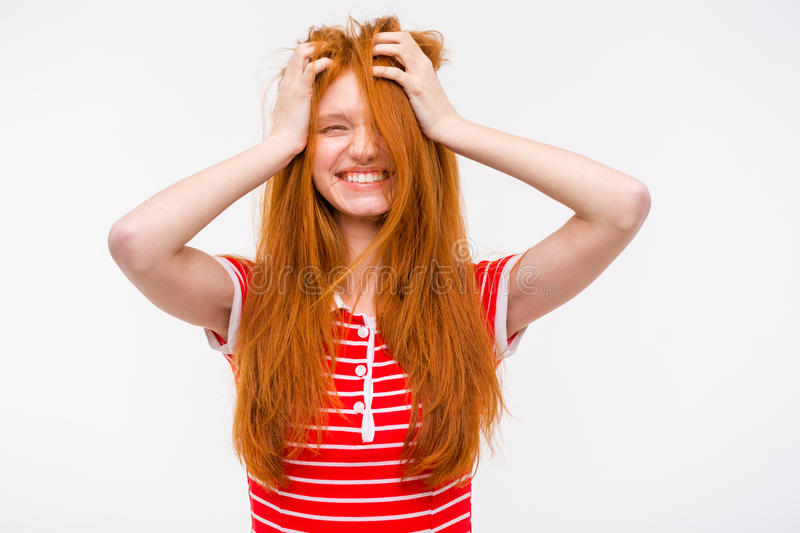 Funny girl with messy tousled hair holding hands to head. Funny amusing cheerful girl with messy tousled long red hair holding her hands to her head and laughing stock image