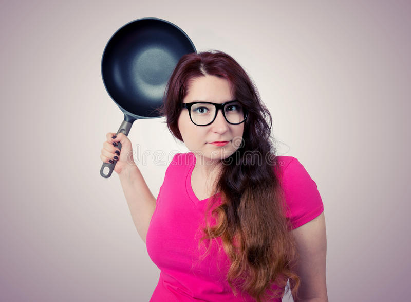 Funny girl in pink with frying pan stock images