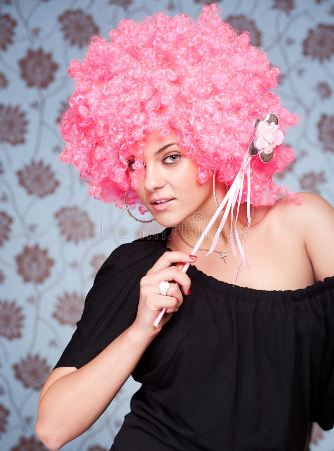 Funny girl in pink wig posing for camera. Across wallpapers background stock images