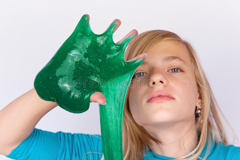 Funny girl playing with green slime looks like gunk on her hand stock images