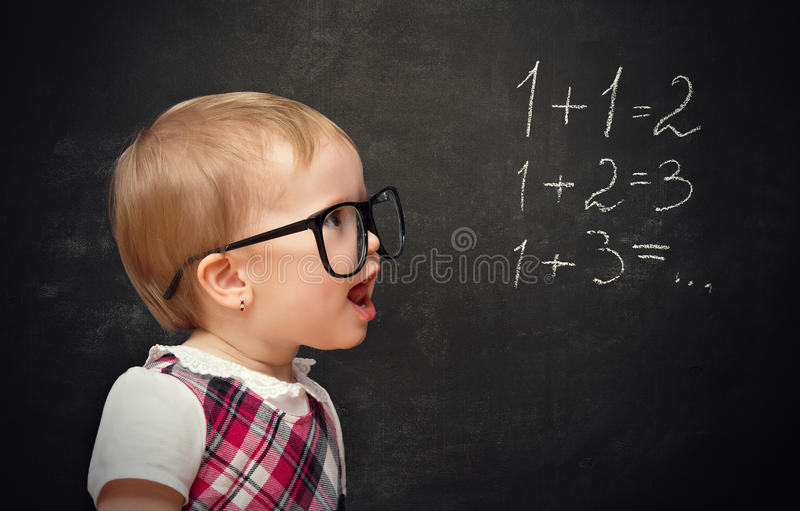 Funny girl pupil solves arithmetic examples. Funny baby girl pupil solves arithmetic examples on blackboard stock photos