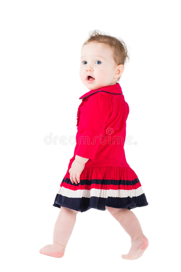 Funny girl in a red dress learning to stand stock image