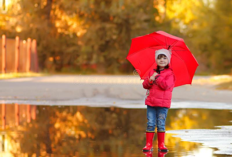 A funny girl with a red umbrella in rubber boots stands in a huge deep puddle and smiles. horizontal photo of the child. warm. Autumn day royalty free stock photos