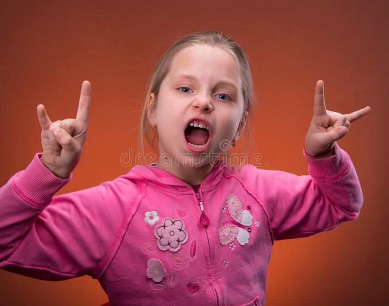 Funny girl rock out. Over the orange background royalty free stock photos
