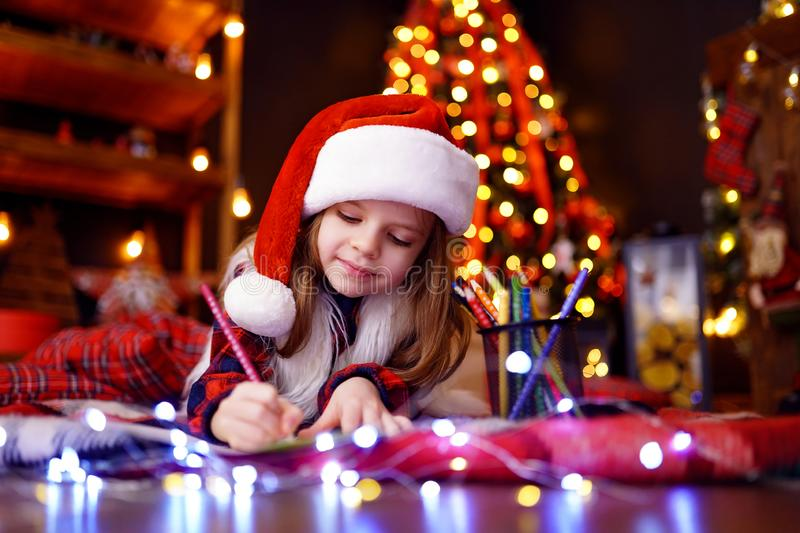 Funny girl in Santa hat writes letter to Santa. Little charming smiling girl in a plaid dress, fur vest, Santa hat is lying on the floor and writes a letter royalty free stock photography