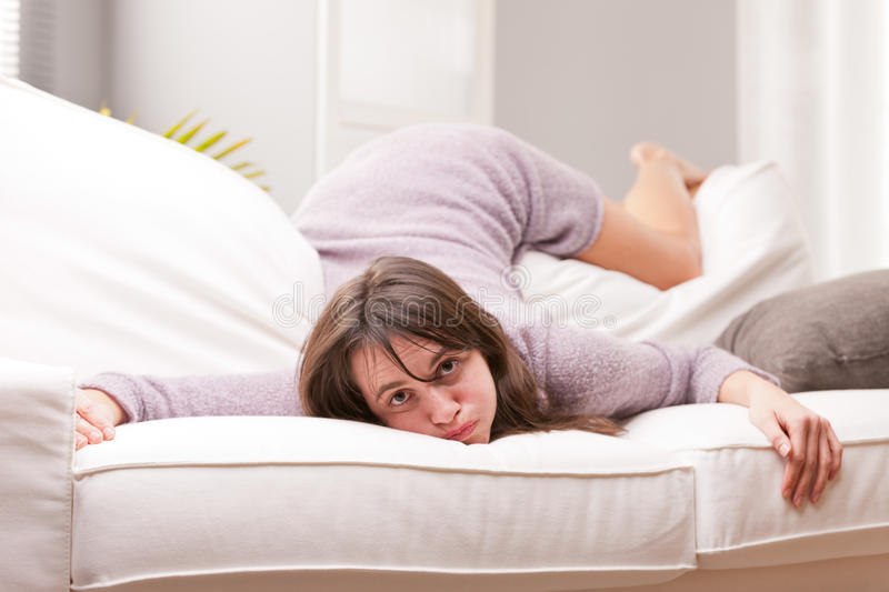 Funny girl showing fatigue on a sofa royalty free stock photography