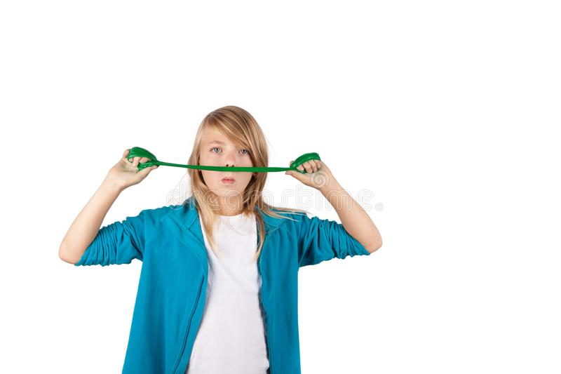 Funny girl stretching a green slime in front of her face. Isolated on white background stock image