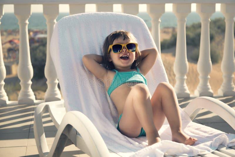 Funny girl sunbathes on a sun lounger. stock photo