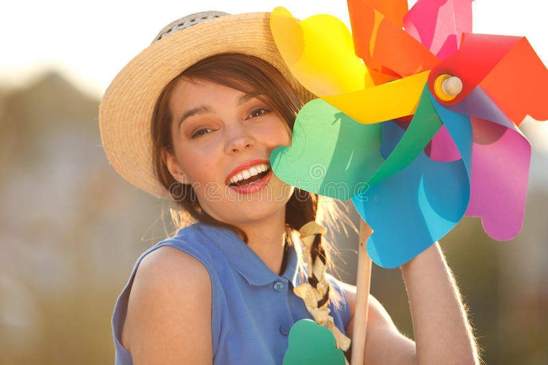 Funny girl with weather vane. Young happy funny (vintage) dressed woman close-up with colorful weather vane,looking like flower Picture ideal for illustating royalty free stock image