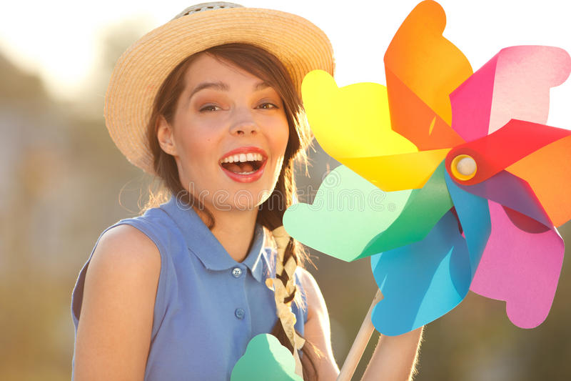 Funny girl with weather vane. Young happy funny (vintage) dressed woman close-up with colorful weather vane,looking like flower Picture ideal for illustating stock photo