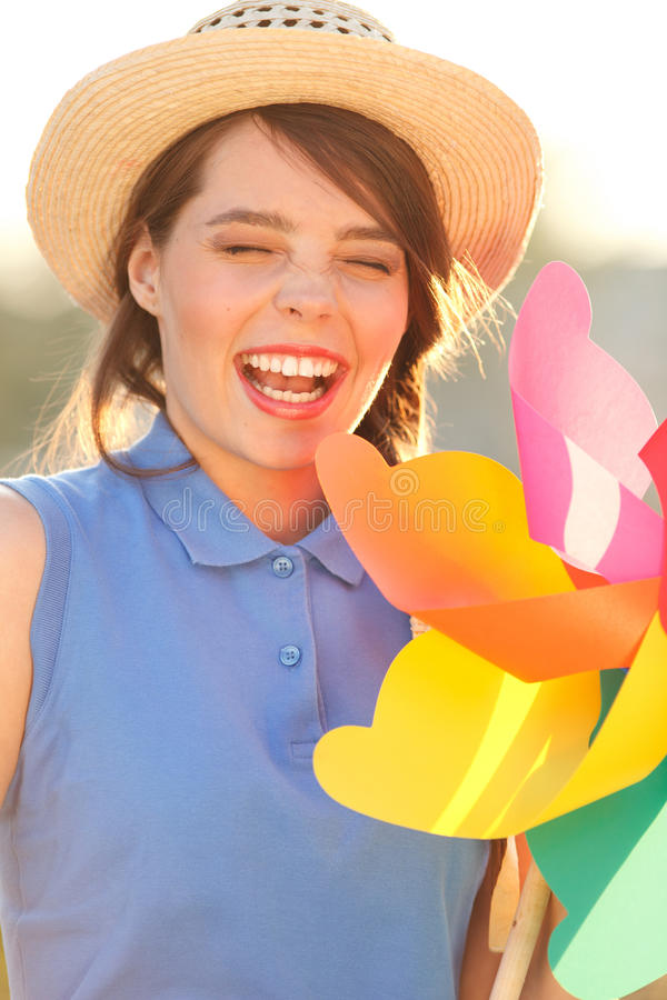 Funny girl with weather vane. Young happy funny (vintage) dressed woman close-up ,making funny face and holding colorful weather vane,looking like flower Picture royalty free stock photography