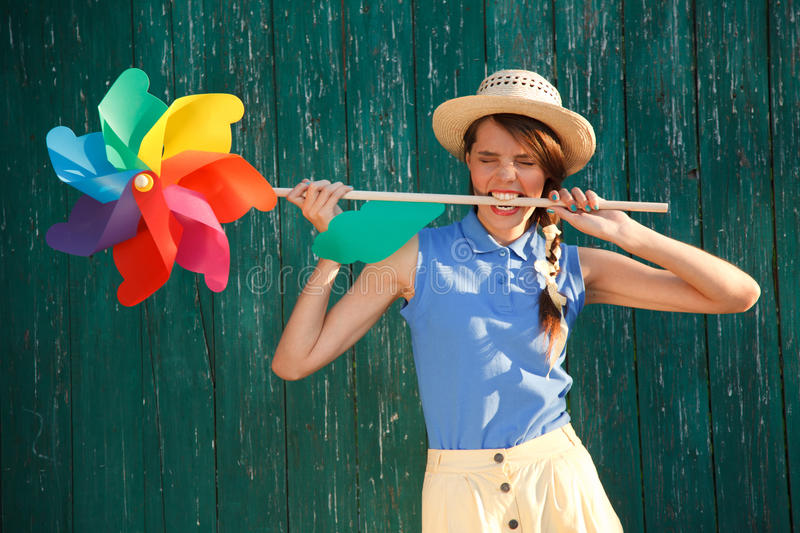 Funny girl with weather vane. Young happy funny (vintage) dressed woman with colorful weather vane in her teeth. Old green fence on the background. Picture ideal stock photo