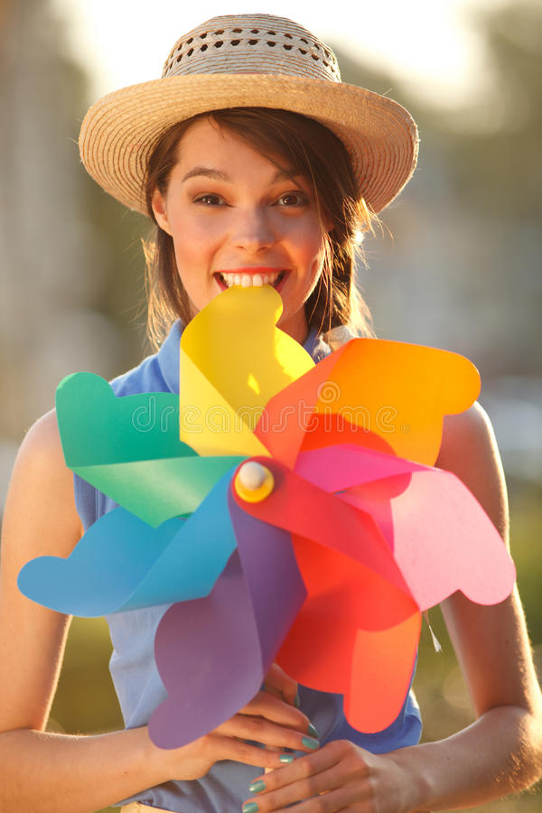 Funny girl with weather vane. Young happy funny (vintage) dressed woman with colorful weather vane in her teeth. Picture ideal for illustating woman magazines stock photos