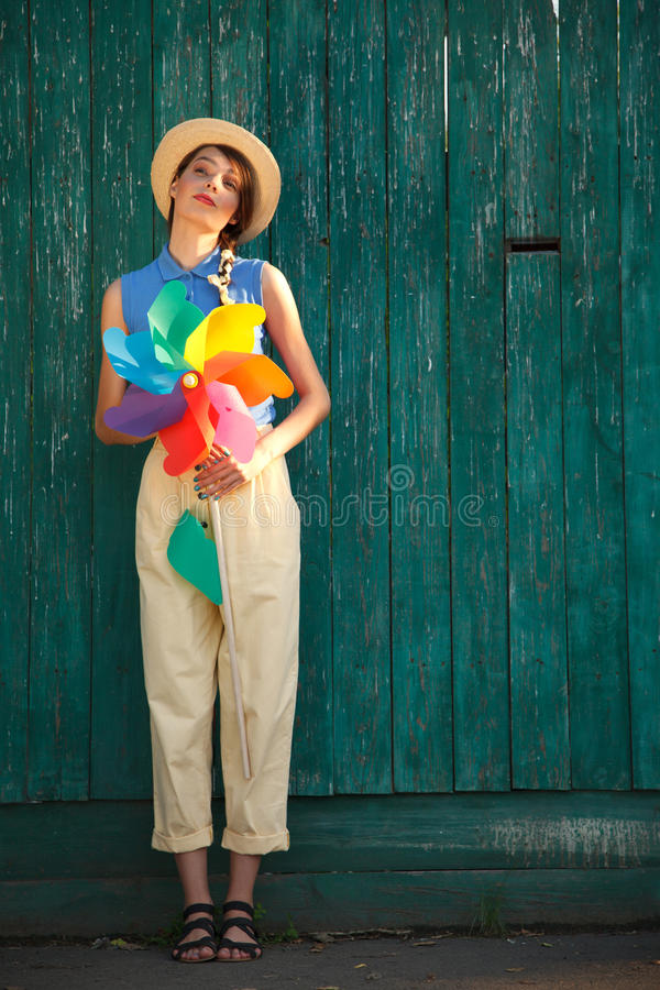Funny girl with weather vane. Young happy funny (vintage) dressed woman with colorful weather vane,looking like flower. Old green fence on the background royalty free stock images