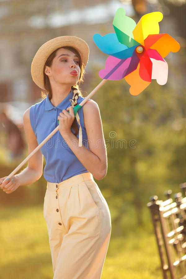 Funny girl with weather vane. Young happy funny (vintage) dressed woman with colorful weather vane,looking like flower Picture ideal for illustating woman stock photography