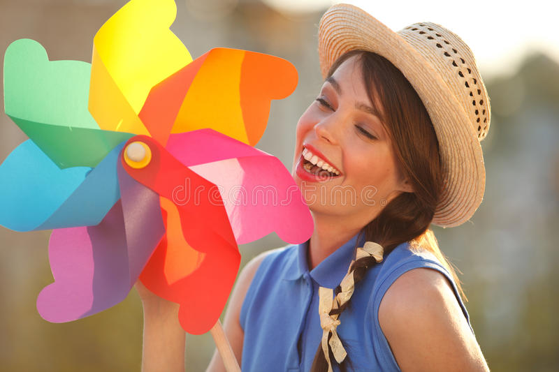 Funny girl with weather vane. Young happy funny (vintage) dressed woman with colorful weather vane,looking like flower Picture ideal for illustating woman royalty free stock photos