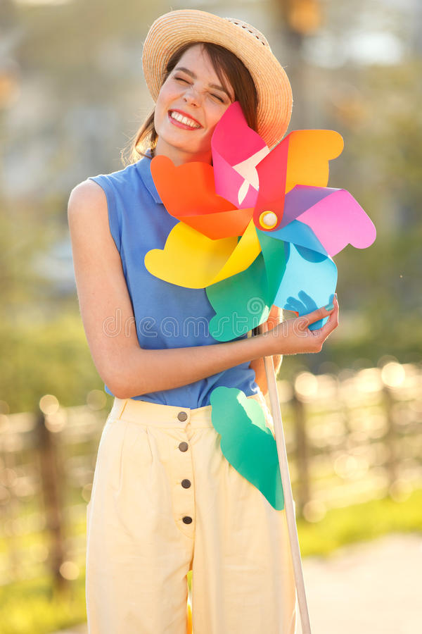 Funny girl with weather vane. Young happy funny (vintage) dressed woman with colorful weather vane,looking like flower Picture ideal for illustating woman royalty free stock photography