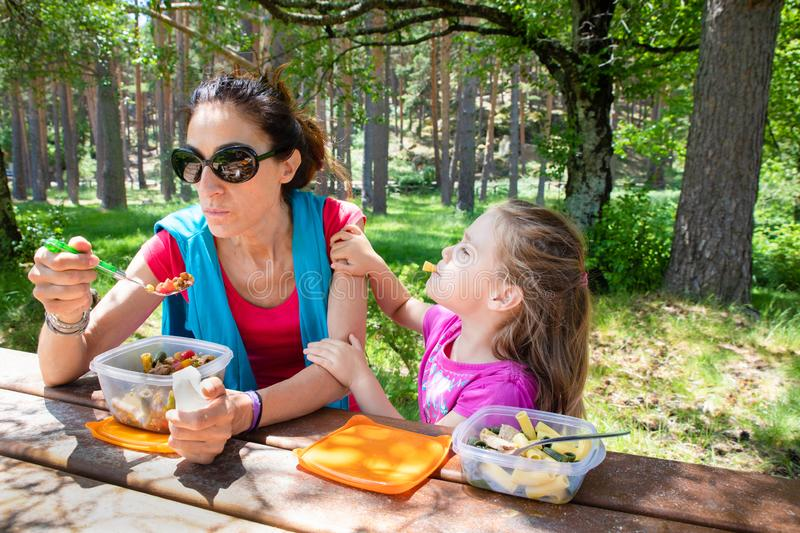 Funny girl and woman eating pasta salad from a plastic lunchbox in a table picnic in the country. Funny scene: four years old blonde girl making fun playing with royalty free stock photography