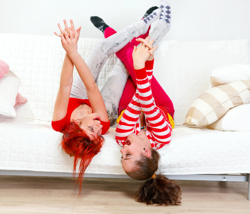 Funny girlfriends in playful mood lying on sofa. Funny young girlfriends in playful mood lying on sofa with legs raised up royalty free stock photo