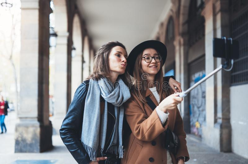 Funny girlfriends taking photo selfie on smartphone mobile. Blogger hipster travels in Barcelona. Holiday friendship kiss concept. Travelers self cellphone stock photo