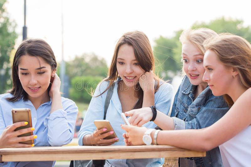 Funny girlfriends use a smartphone and laugh at the table of a summer cafe royalty free stock images
