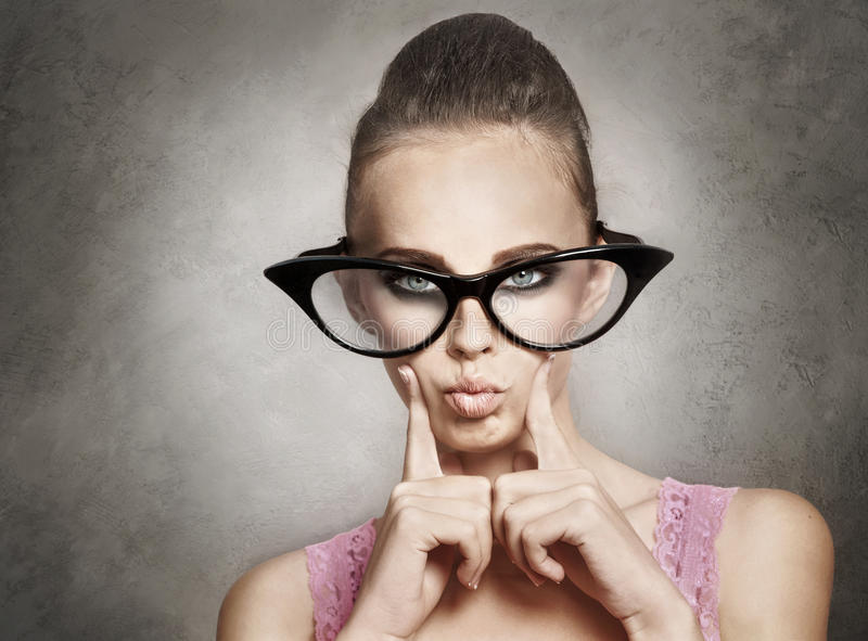 Funny glasses. Grimace of charming young woman in large funny glasses stock photography