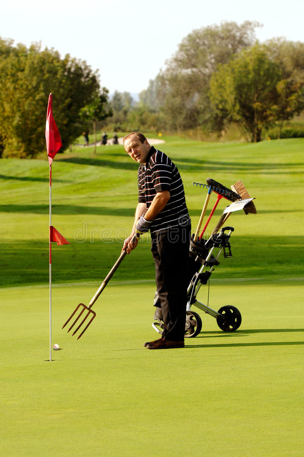 Funny Golfer. Funny Male Golfer Playing Golf With Pitchfork stock photography