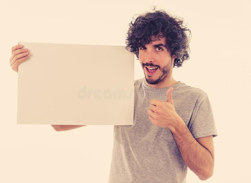 Young funny man holding blank board for advertisement. Millennial men pointing at white billboard royalty free stock photos