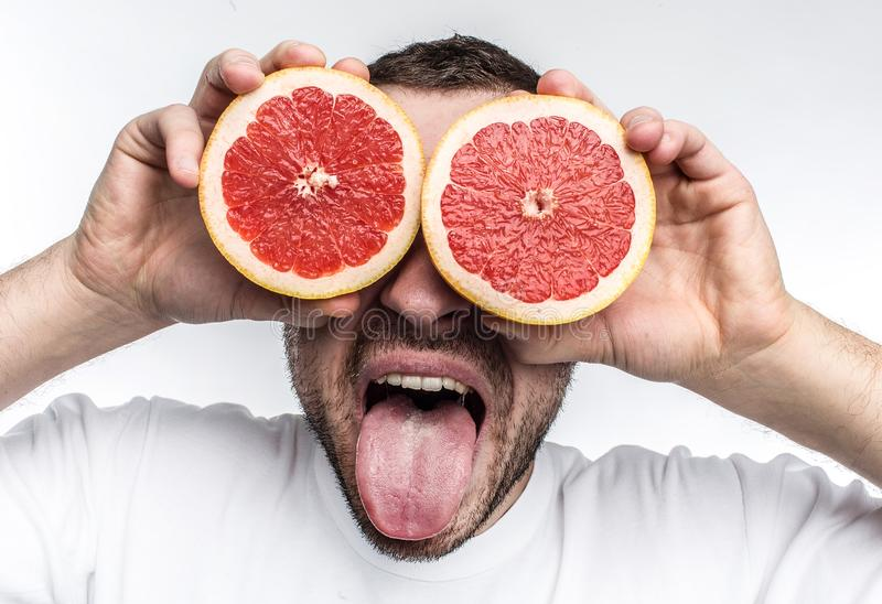 Funny and good picture of adult man putting two half pieces of grapefruit onto his eyes. Also he is showing his tongue royalty free stock photos