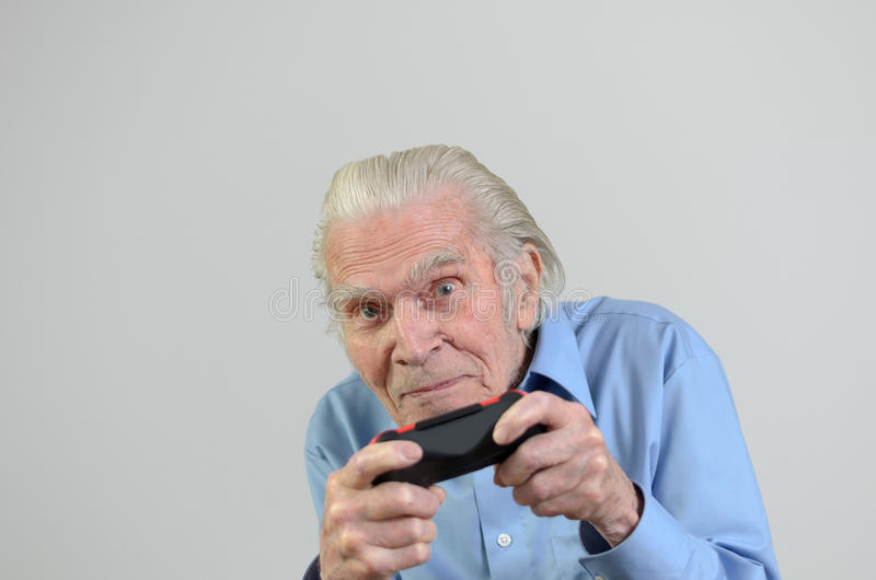 Funny grandfather playing a video game on console royalty free stock images