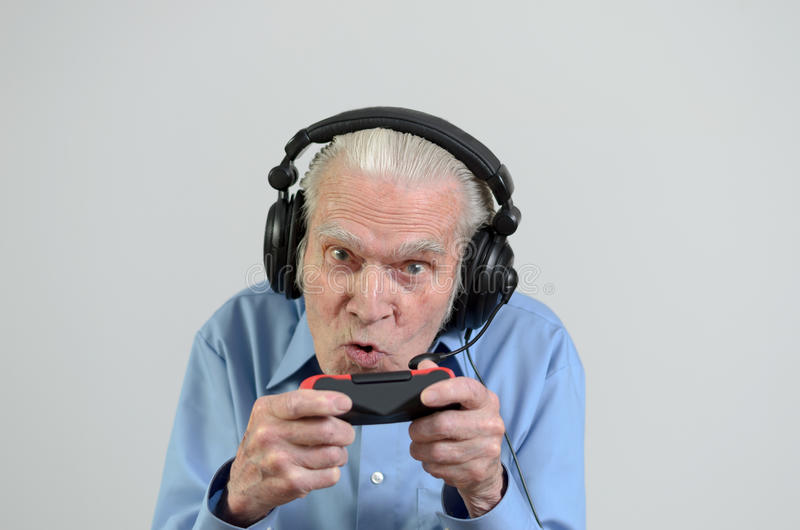 Funny grandfather playing a video game on console. Funny elderly man or grandfather using black headset with headphones and microphone while playing a video game stock photo