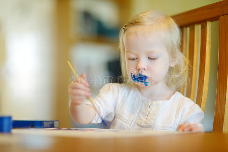 Funny grimy toddler girl painting. In daycare royalty free stock image