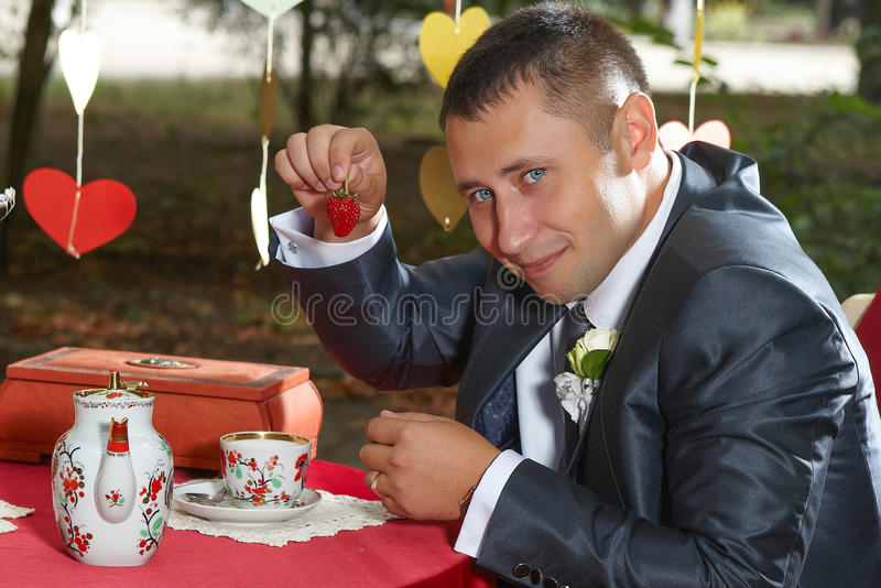 Funny groom with strawberries royalty free stock photography