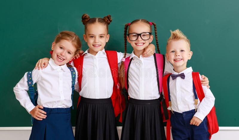 Funny group children   schoolboy  and schoolgirl, student boy  and girl about school blackboard stock image