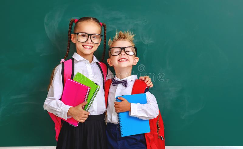 Funny group children   schoolboy  and schoolgirl, student boy  and girl about school blackboard royalty free stock images