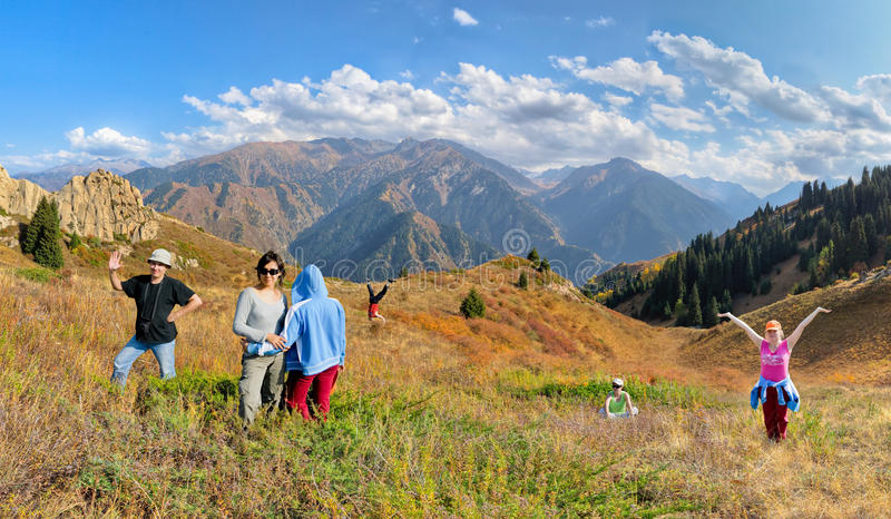 Funny group of people hiking on the meadow of mountain royalty free stock photography