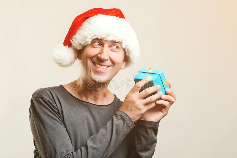 Funny guy with christmas hat holds small present. New Year Holiday. Christmas, x-mas, winter gifts concept. Man wearing Santa Clau stock photo
