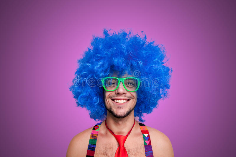 Funny guy naked with blue wig and red tie. On pink backgrund stock image