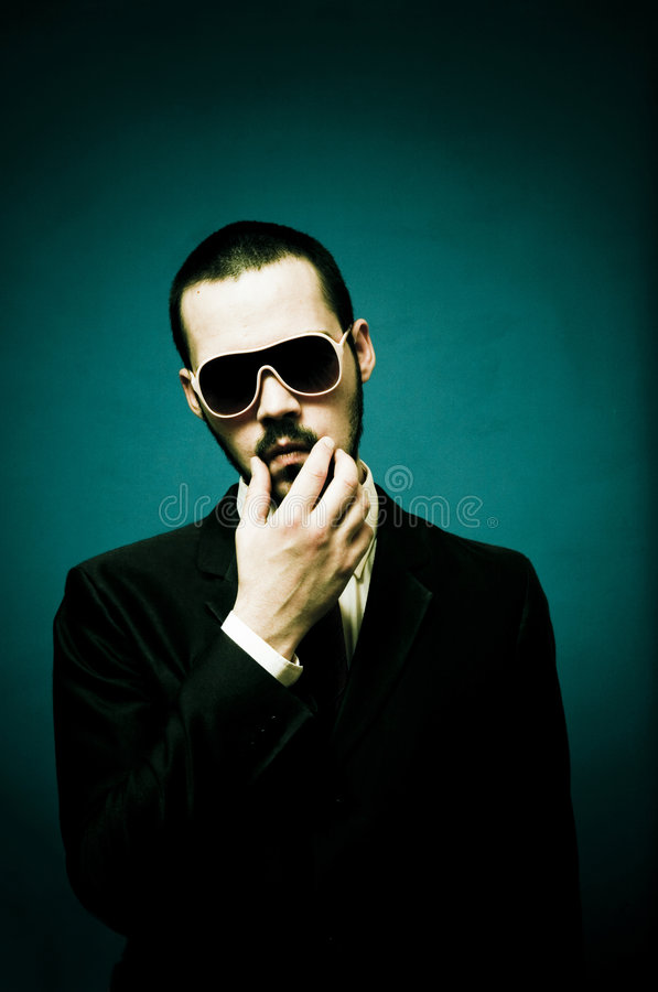 Funny Guy in Suit. Guy in suit, mobster-like look, aqua background, wearing sunglasses, touching face and stroking mustache stock photos