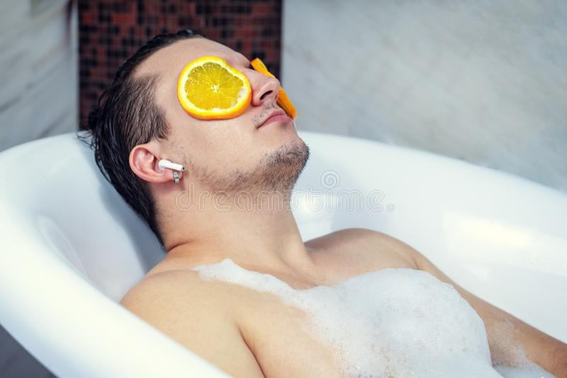 Funny guy washing his bath. Listens to music with wireless headphones. Relaxed from spa procedures on face with orange round slice. S royalty free stock image