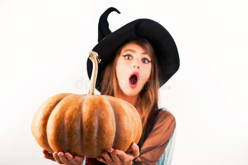Funny Halloween face and Surprised woman. Woman posing with Pumpkin. Beautiful young surprised woman in witches hat and stock photography