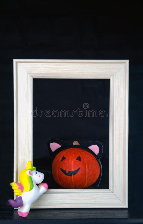 Funny Halloween. Pumpkin baby in white frame and with unicorn on the black background. Halloween concept with copy space. stock photography
