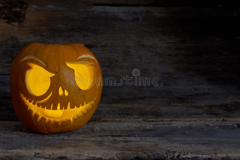 Funny Halloween pumpkin face with glowing candle. Carved pumpkin head with burning candle on old woden background royalty free stock images