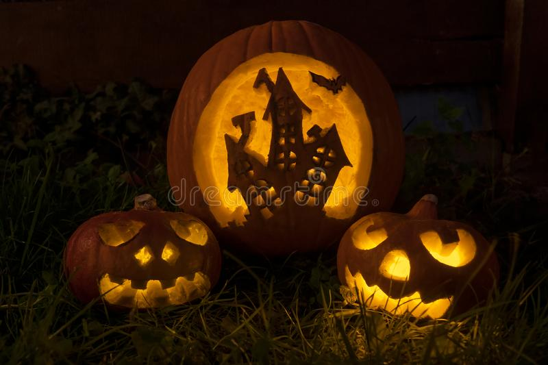 Funny halloween pumpkins with scary house and faces stock image