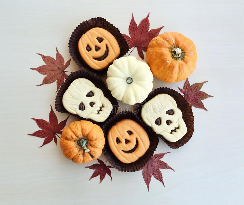 Funny Halloween sandwich cookies and mini pumpkins royalty free stock photo