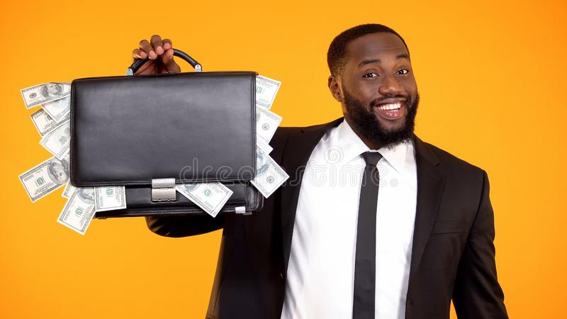 Funny handsome afro-american businessman showing handbag with dollar cash, money stock image