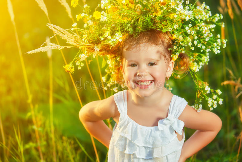 funny happy baby child girl in a wreath on nature laughing in summer stock photo